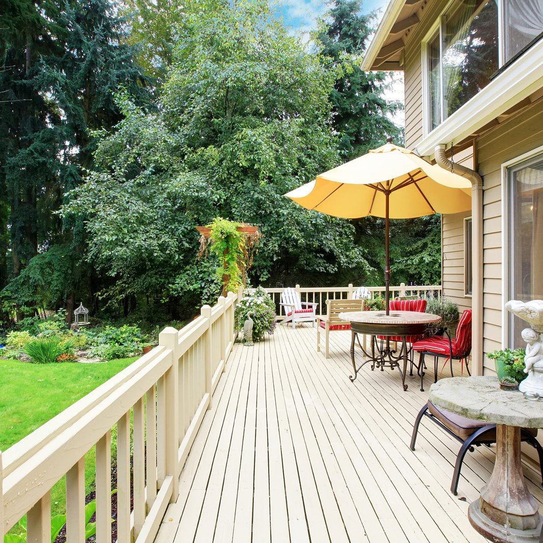 Wooden walkout deck with patio area overlooking backyard landscape